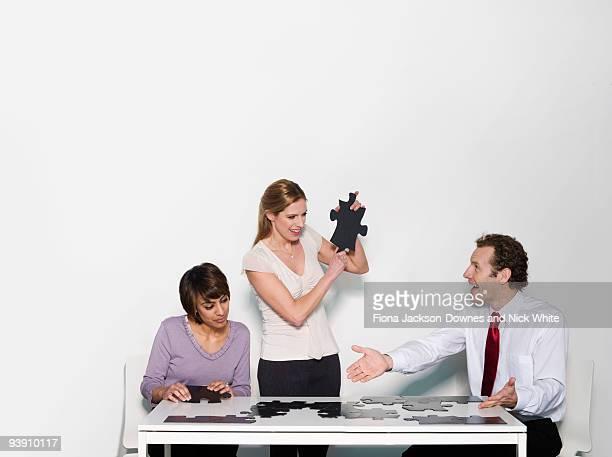A business trio doing a jigsaw