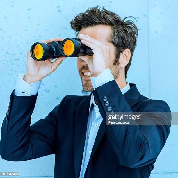 vision des affaires: Homme tenant une paire de jumelles