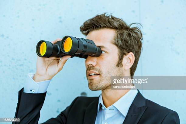 Business vision: man holding binoculars