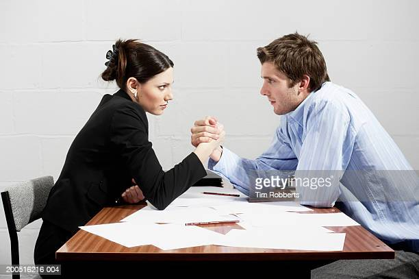 Business woman and business man arm wrestling over table, side view