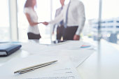 Business woman and business man shaking hands with a contract.