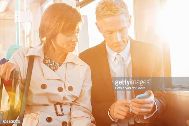 Business woman and man on train , checking phone.