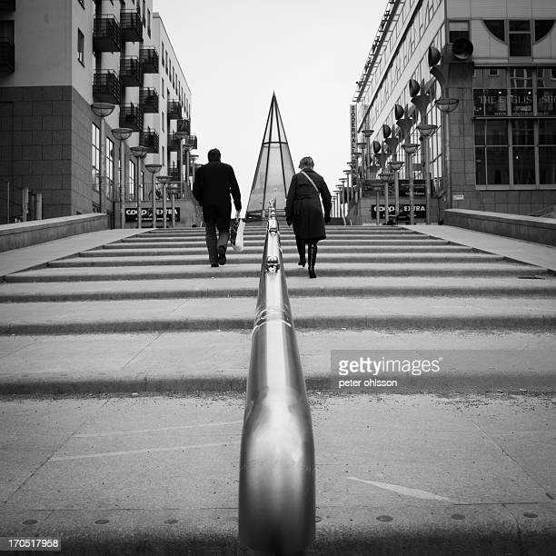 Business woman and man walking up the stairs divided by a rail.