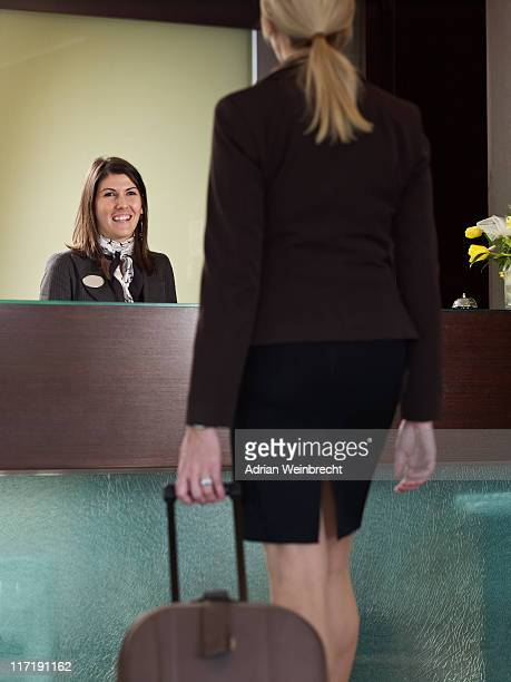 Business Frau aproaching Portier an der Rezeption