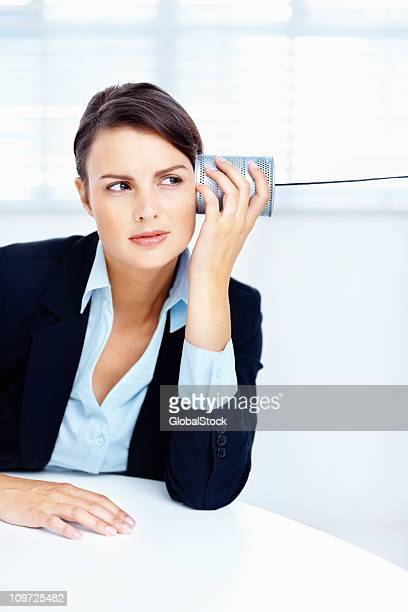 Business woman at a table listening to tin can
