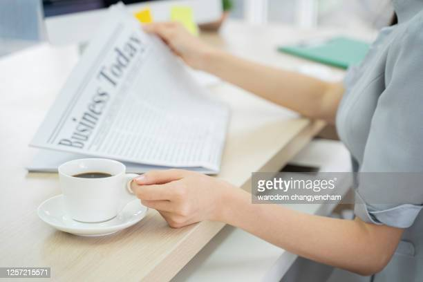 business woman at office reading newspaper. - article stock pictures, royalty-free photos & images