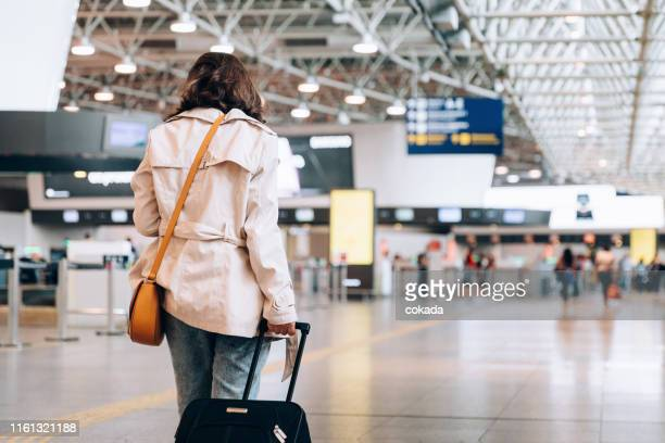 business woman at the airport with carry on luggage - coat stock pictures, royalty-free photos & images