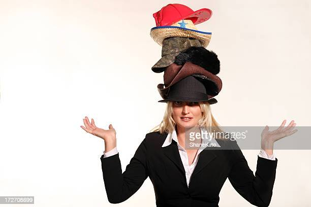 business woman balancing life having to wear too many hats - hat stock photos and pictures