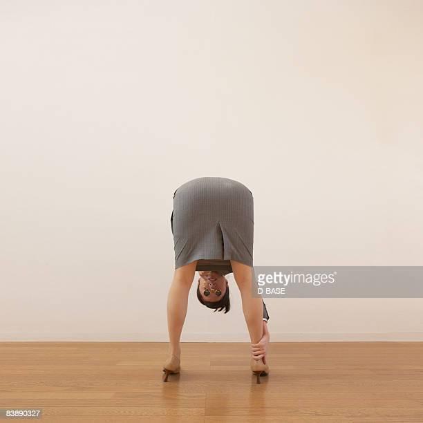 business woman bending over, looking between legs