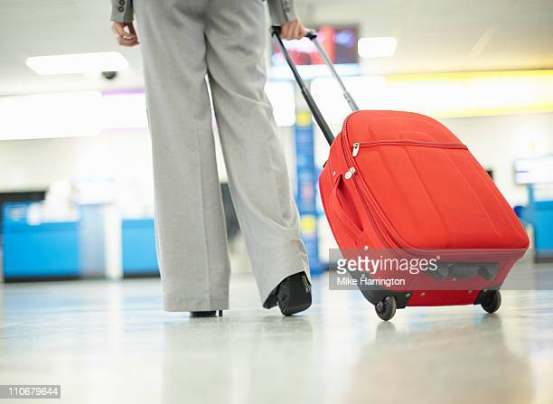 business woman carrying luggage - wheeled luggage stock photos and pictures