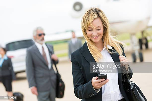 Business woman checking cell phone and smiling.