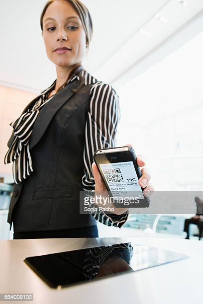 Business woman checking in at airport security gate with smart phone