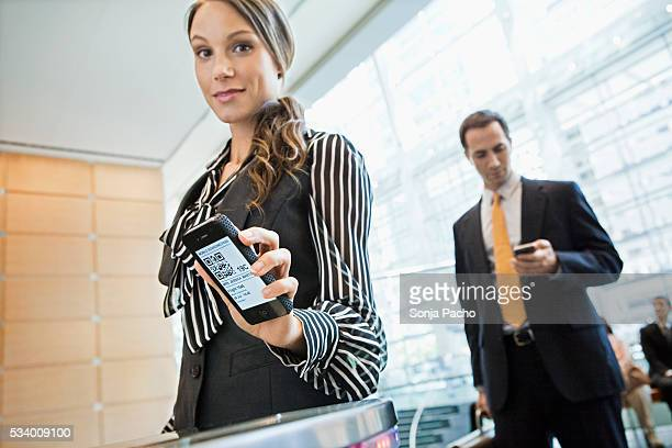 Business woman checking in with smart phone at airport gate