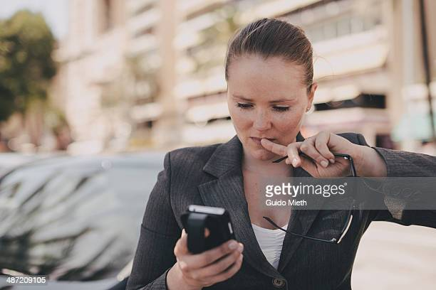 Business woman checking mails outdoor.