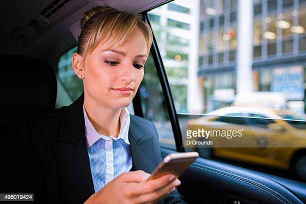 Business woman checking phone in car