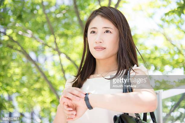 Business woman checking time on wrist watch