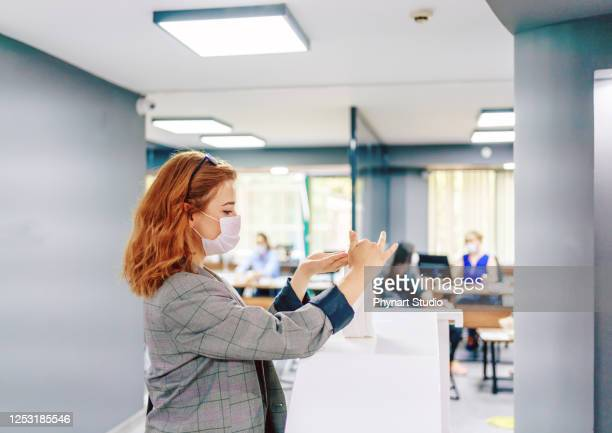 business woman cleaning hands with sanitizer in the office - reopening stock pictures, royalty-free photos & images