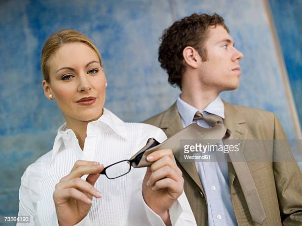 Business woman cleaning spectacles with man's tie