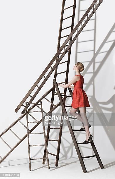 Business woman climbing up ladder construction