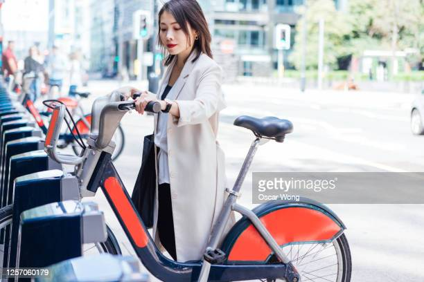 business woman commuting to work by bicycle - business stock pictures, royalty-free photos & images