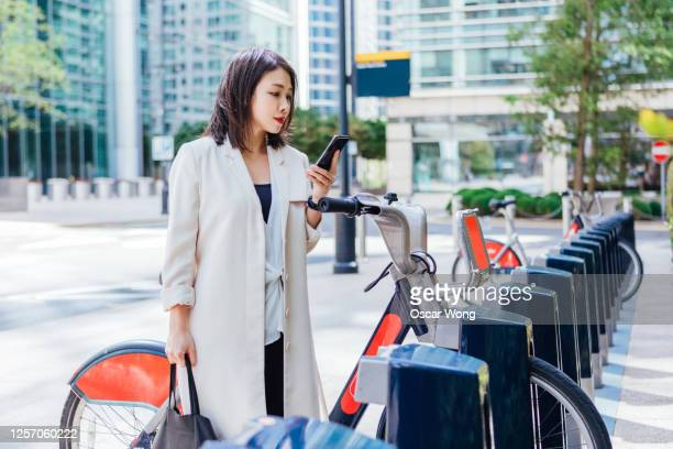 business woman commuting to work by bicycle - paying stock pictures, royalty-free photos & images