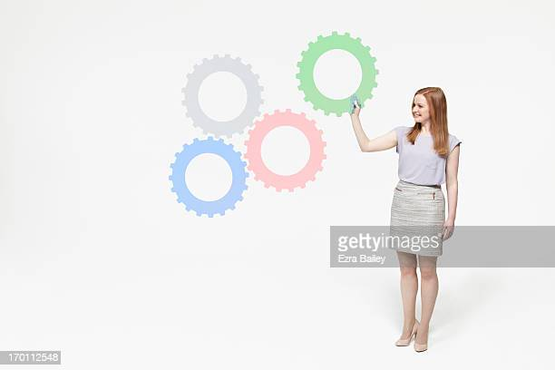 Business woman completing a system of cogs.