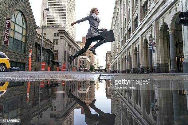 Business woman crosses city street after rain