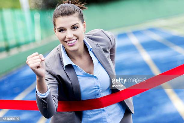 Business woman crossing finish line