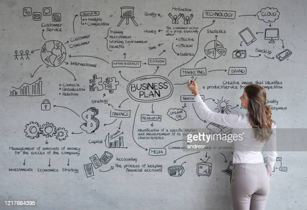 business woman drawing a business plan at the office - business plan stock pictures, royalty-free photos & images