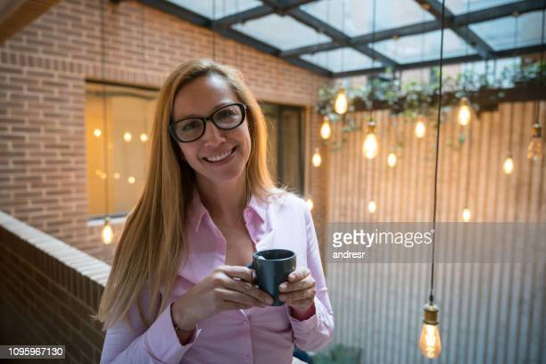 Business woman drinking coffee at a co-working space