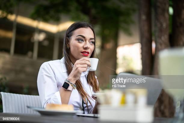 zakenvrouw koffie drinken in cafe - alleen mid volwassen vrouwen stockfoto's en -beelden