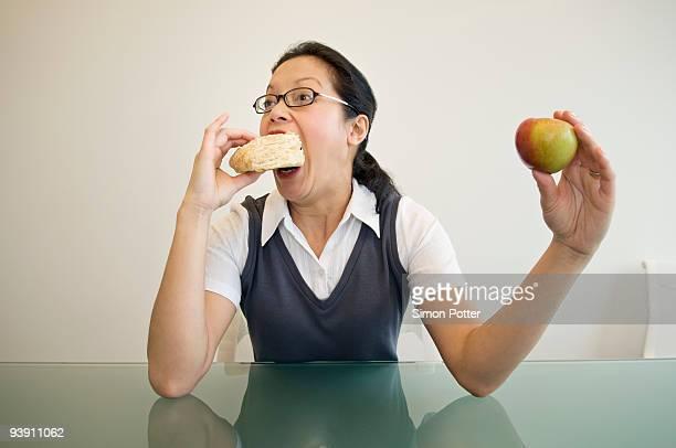 a business woman eating a sandwich - abbuffata foto e immagini stock
