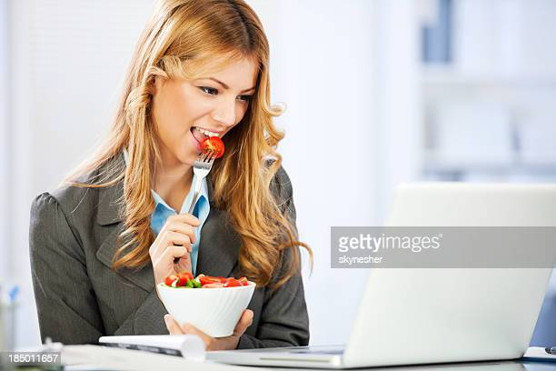 Business woman eating salad and using laptop.