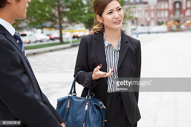 Business woman explaining to colleagues in town