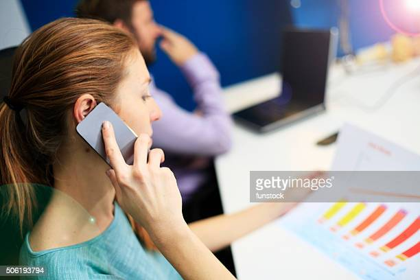 Business woman explains financial report over the phone