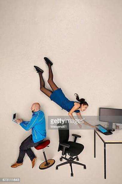 business woman flying towards office desk, male colleague sitting and working - hovering stock pictures, royalty-free photos & images