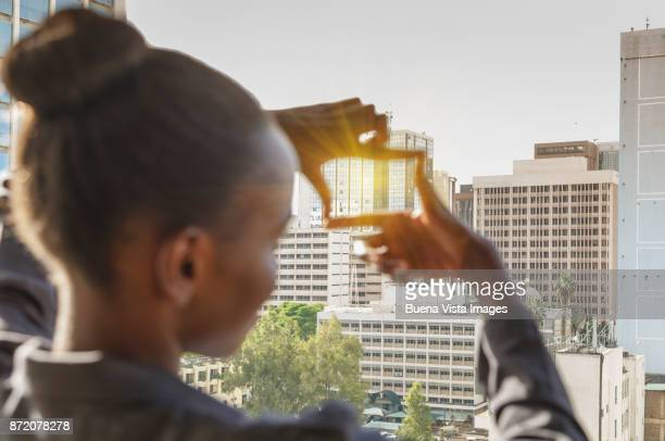 Business woman framing building with fingers