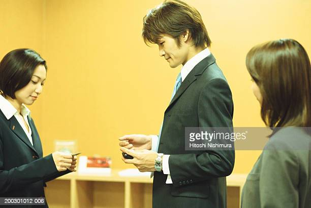 Business woman giving business card to man, side view