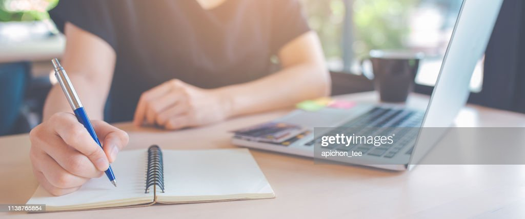 Business woman hand is writing on a notepad with a pen. : Stock Photo