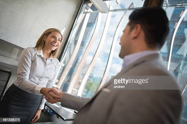 business woman handshaking with a client - sluiten stockfoto's en -beelden