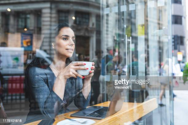business woman having a coffee and looking out of the window - on the move stock pictures, royalty-free photos & images
