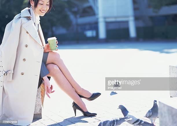 business woman having coffee break - トレンチコート ストックフォトと画像