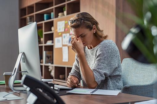 Business woman having headache at office 1059661102