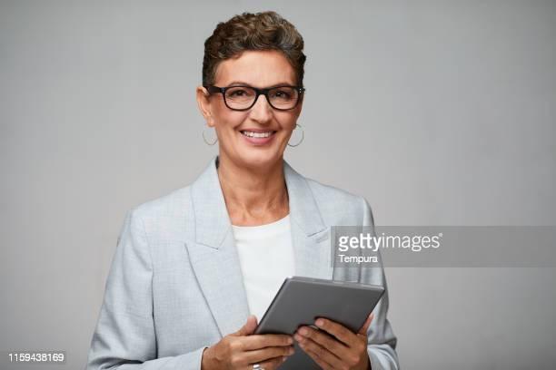 femme d'affaires retenant une tablette numérique et portant des glaces. - femme espagnole photos et images de collection