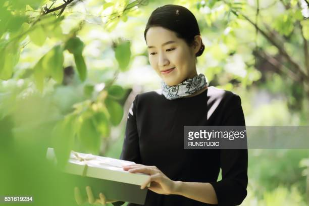 business woman holding a gift and looking down with smile,