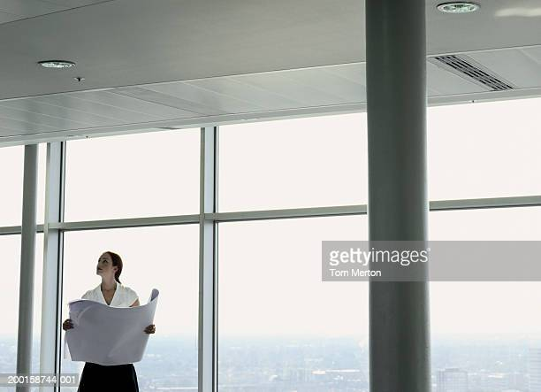 Business woman holding plans, looking at office ceiling