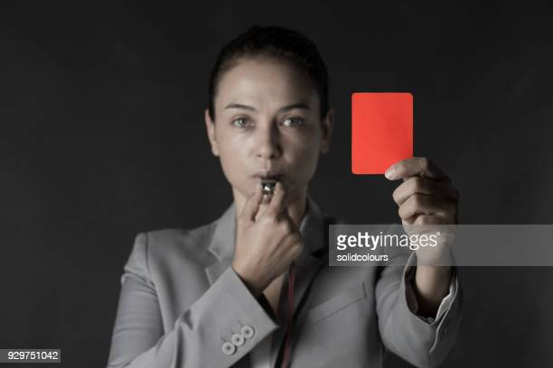 business woman holding red card and blowing a whistle - whistle stock pictures, royalty-free photos & images