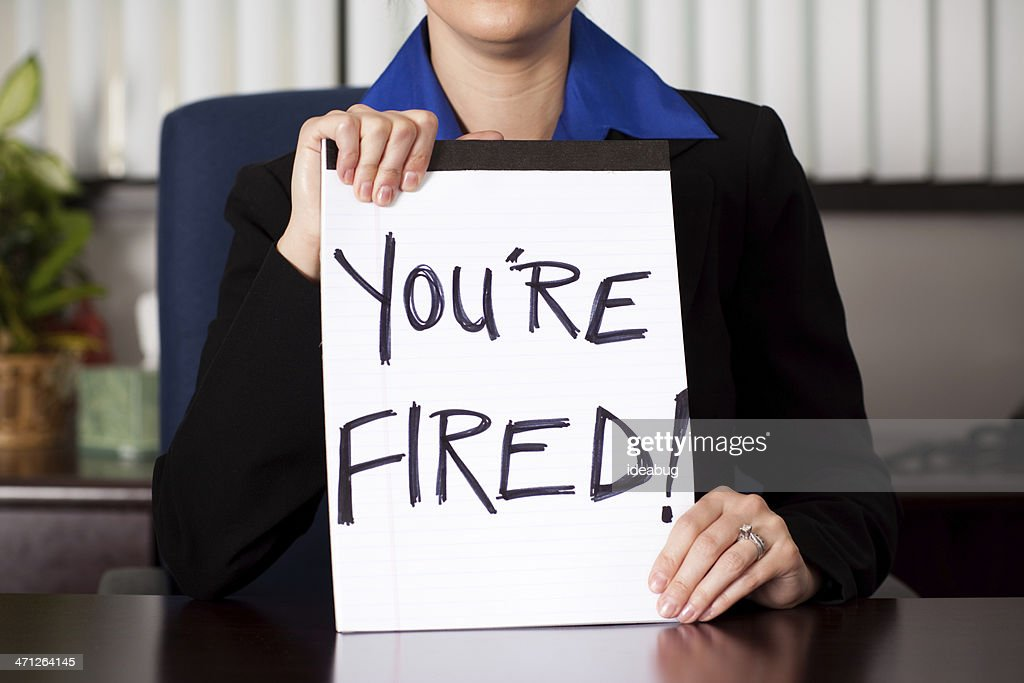"Business Woman Holding ""You're Fired"" Sign at Desk : Stock Photo"