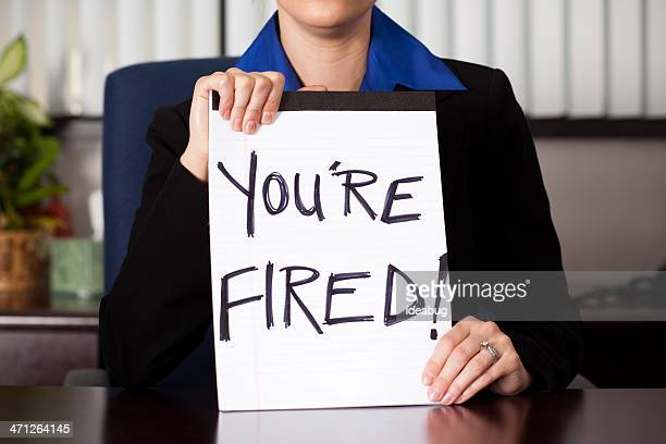 """business woman holding """"you're fired"""" sign at desk - being fired stock photos and pictures"""