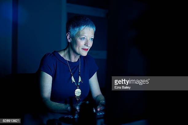 Business woman illuminated by a computer screen.